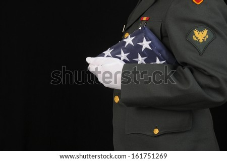 Soldier holding folded flag/Soldier Honor/Man in US Army uniform holds a ceremonial flag - stock photo