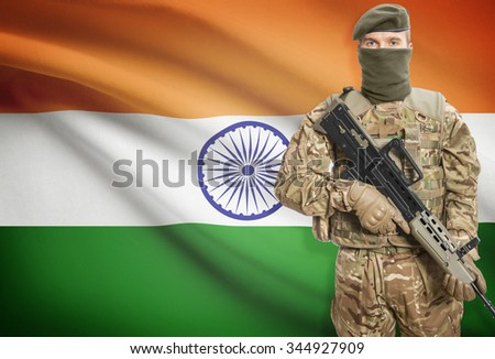 Soldier holding machine gun with national flag on background - India - stock photo