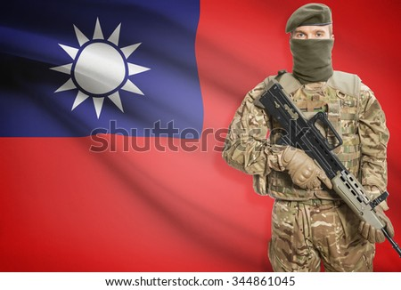 Soldier holding machine gun with national flag on background - Taiwan - stock photo