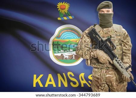Soldier holding machine gun with USA state flag on background - Kansas - stock photo