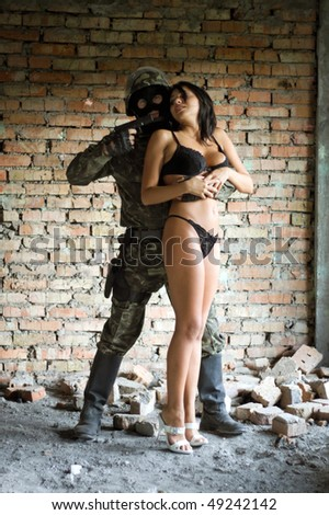 Soldier holding pretty woman in underclothes hostage