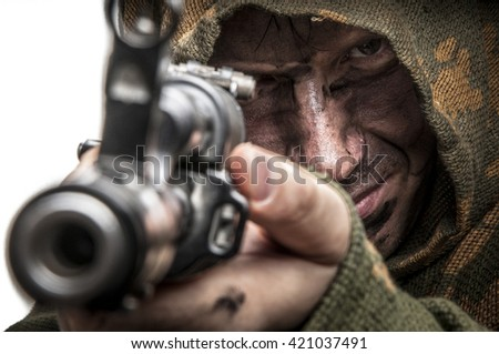 Soldier in camouflage aiming with a gun - stock photo