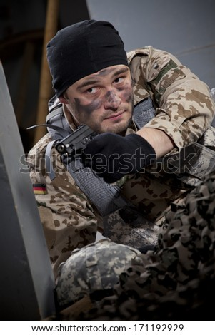 Soldier in camouflage hiding in ruins and aiming with a gun - stock photo