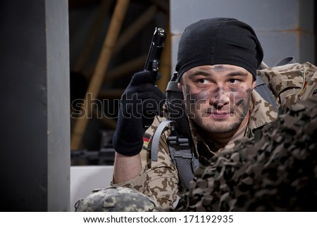 Soldier in camouflage hiding in ruins holding a gun - stock photo