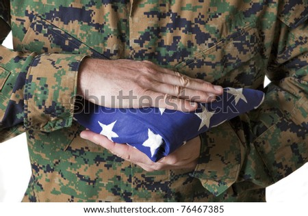 Soldier in Camouflage Holding Flag - stock photo