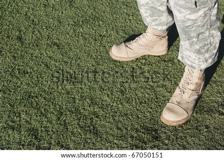 Soldier in camouflage pants and army boots. - stock photo