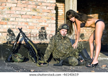 Soldier in camouflage resting with sexy woman - stock photo