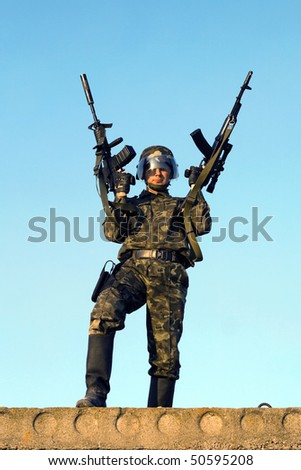 Soldier in camouflage staying with two rifles - stock photo