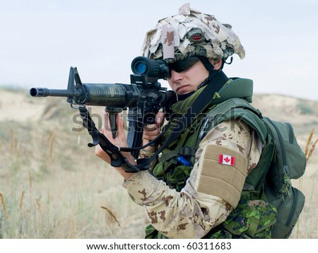 soldier in desert uniform aiming his rifle - stock photo
