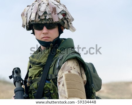 soldier in desert uniform holding his rifle