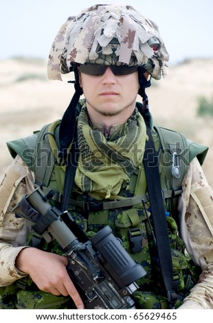 soldier in desert uniform holding his rifle - stock photo