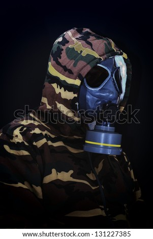 Soldier in gas mask on black background - stock photo