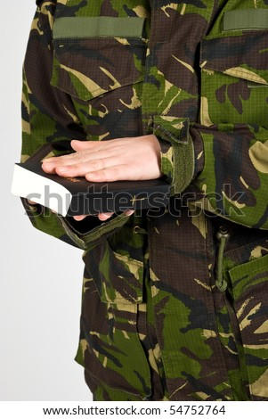 Soldier in the army swear with hand on bible to defend the country isolated on white background - stock photo