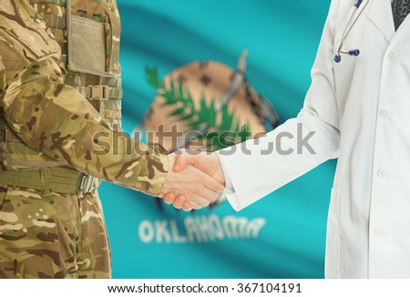 Soldier in uniform and doctor shaking hands with US states flags on background - Oklahoma - stock photo