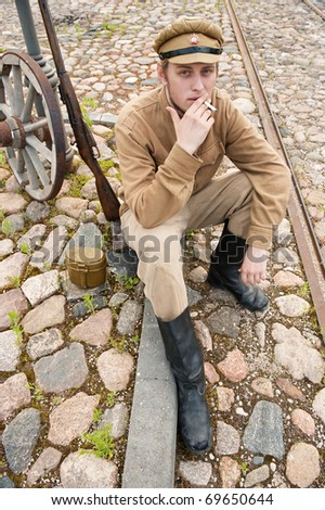 Soldier in uniform of World War I, sit down, resting on the pavement and smoking. Costume accord the times of World War I. Photo made at cinema city Cinevilla in Latvia. - stock photo