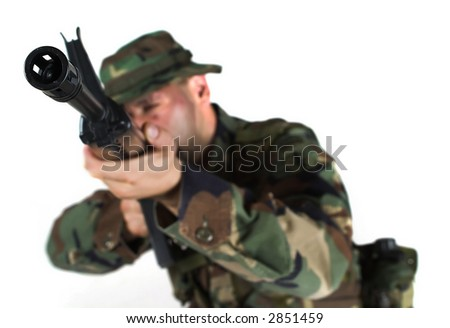 Soldier is aiming. The focus is placed to the muzzle while the man himself is out of focus in anonymity. - stock photo