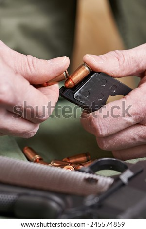 Soldier load ammo in the clip Colt - stock photo