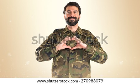 Soldier making a heart with his hands  - stock photo