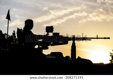 soldier on a tank with an automatic rifle - stock photo