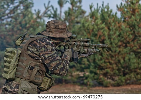 Soldier on battle field, aiming. - stock photo