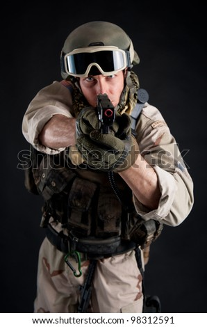 Soldier pointing gun against black background. - stock photo