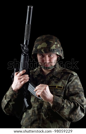 Soldier reloading magazine of m16 in studio. Isolated - stock photo