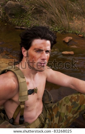 Soldier rest by a creek during training - stock photo