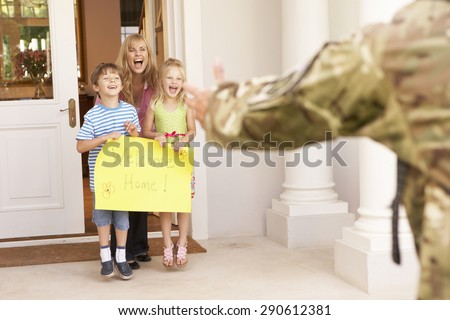Soldier Returning Home And Greeted By Family - stock photo