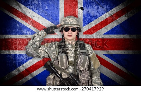 soldier salutes the england flag on the background - stock photo