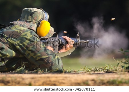 Soldier shooting rifle gun to target with bullet cartridge in the air