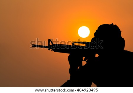 Soldier shooting with his weapon on sunset background.