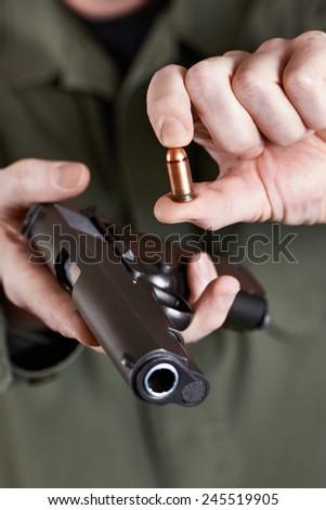 Soldier shows pistols Colt and ammunition closeup - stock photo