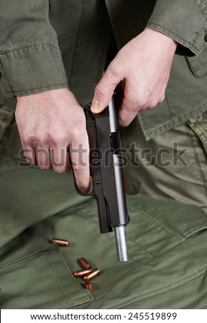 Soldier shutter cocking pistol gun Colt and cartriges - stock photo