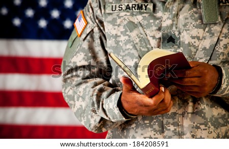 Soldier: Soldier Reading And Paging Through Bible - stock photo