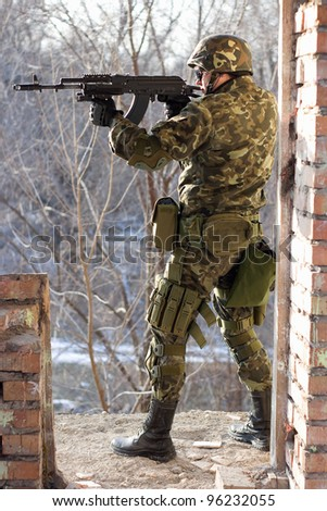 Soldier standing near wall with a gun in his hands - stock photo