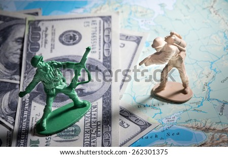 Soldier toys on money and map. - stock photo