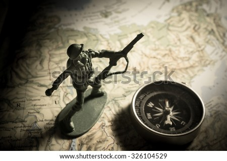Soldier toys with compass on map - stock photo