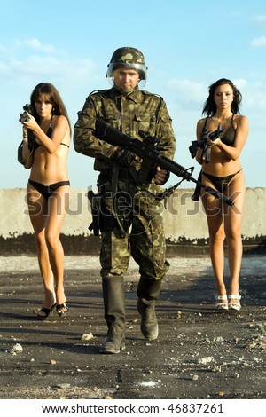 Soldier walking with two young women. Focus on man