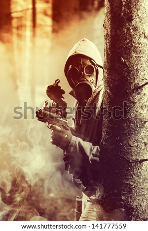 Soldier wearing a gas mask is fighting for its survival - stock photo