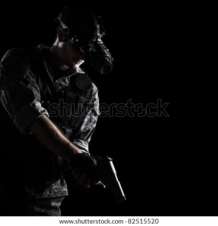 soldier wearing urban camouflage uniform with night vision goggles armed with a gun on black background - stock photo