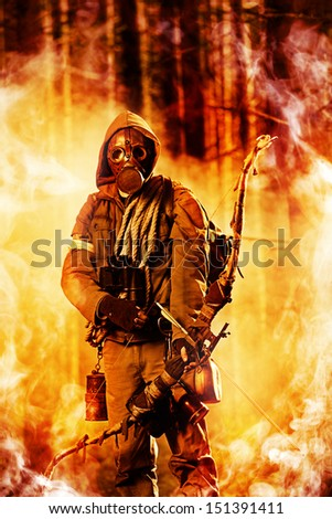 Soldier with a bow in a forest on fire - stock photo