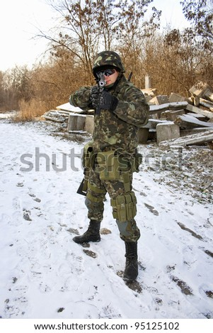 Soldier with a gun in his hands - stock photo
