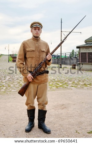 Soldier with a gun in uniform of World War I. Costume accord the times of World War I. Photo made at cinema city Cinevilla in Latvia. - stock photo