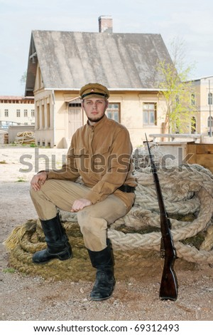 Soldier with a gun in uniform of World War I, sit down on the rope. Costume accord the times of World War I. Photo made at cinema city Cinevilla in Latvia. - stock photo