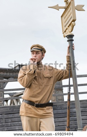 Soldier with a gun in uniform of World War I, smoking at tram stop. Costume accord the times of World War I. Photo made at cinema city Cinevilla in Latvia. - stock photo