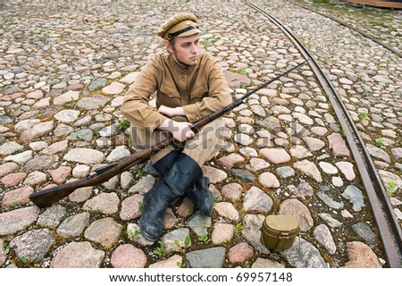 Soldier with gun and boiler in uniform of World War I, sit down and resting on the pavement. Costume accord the times of World War I. Photo made at cinema city Cinevilla in Latvia. - stock photo