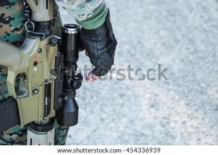 soldier with guns and the cigarette in her hand close-up - stock photo