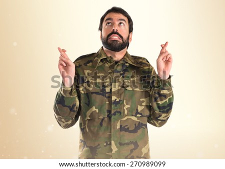 Soldier with his fingers crossing   - stock photo