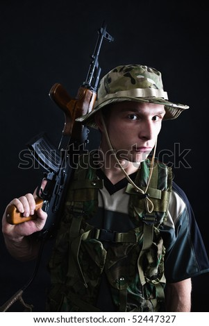 Soldier with Kalashnikov rifle on shoulder, dark background