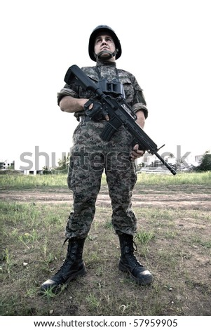 Soldier with the rifle and binocular in camouflage uniform and cask - stock photo